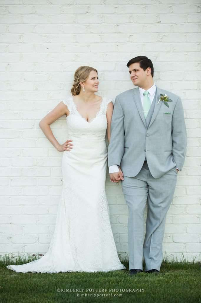 bride and groom leaning against a white brick wall looking at each other smiling