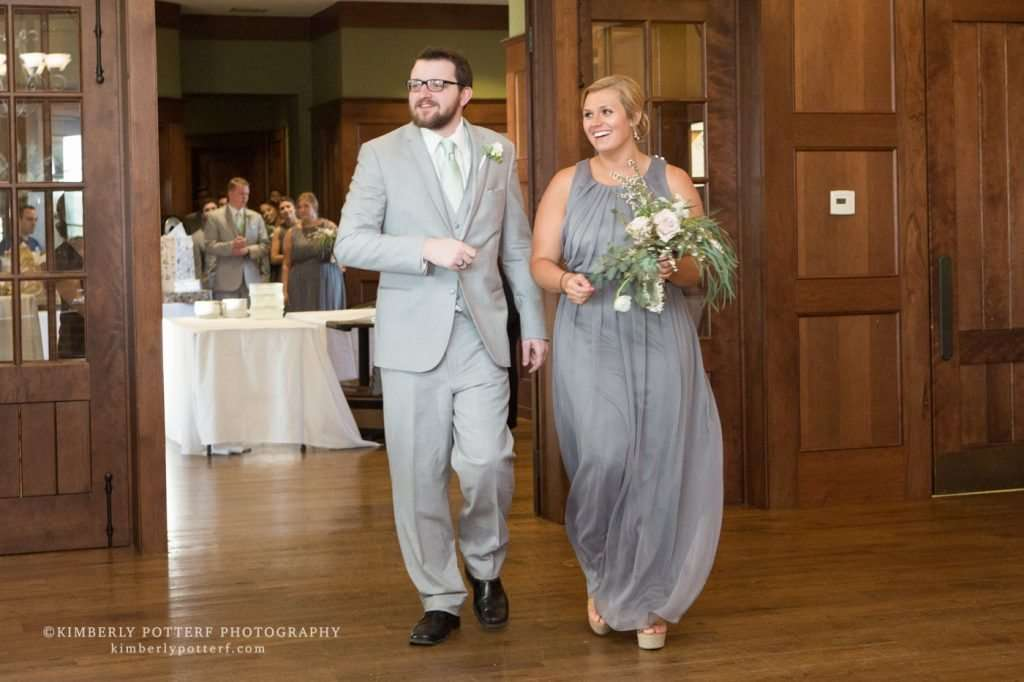 candid shot of a bridesmaid and groomsman smiling and entering the wedding reception of the Golf Club of Dublin