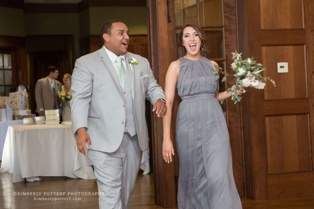 candid shot of a bridesmaid and groomsman laughing while entering the wedding reception of the Golf Club of Dublin