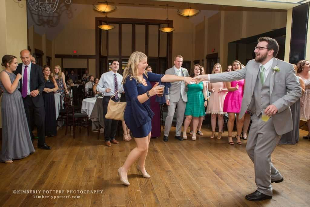 guests dancing and laughing at a wedding reception