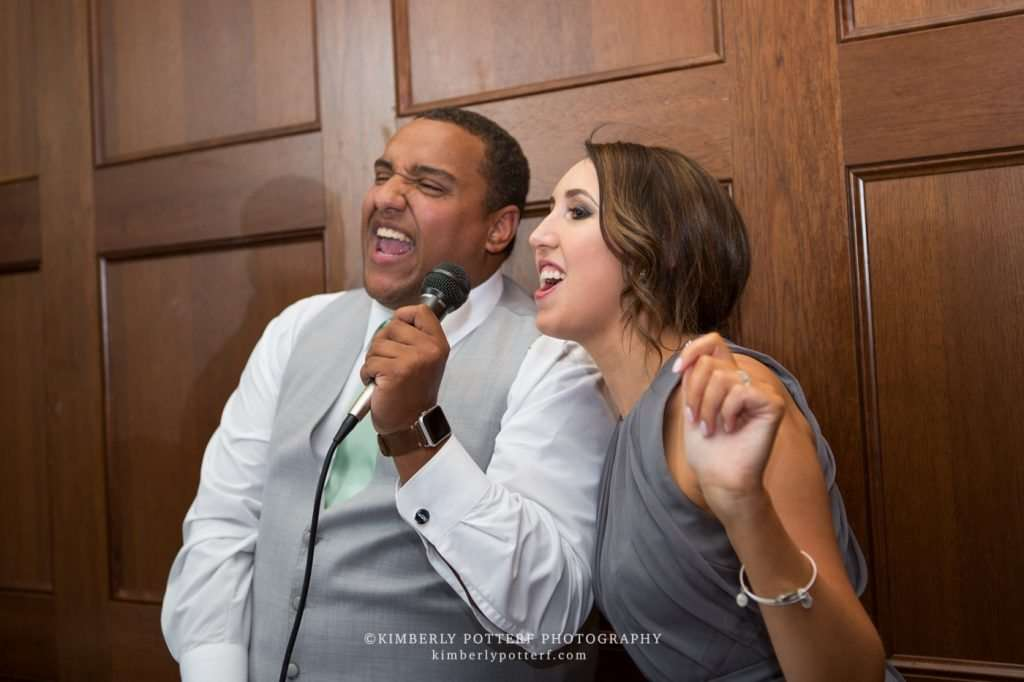 the maid of honor and best man singing a funny duet at a wedding reception