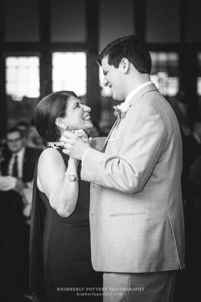 a groom laughs and shares a dance with his mom
