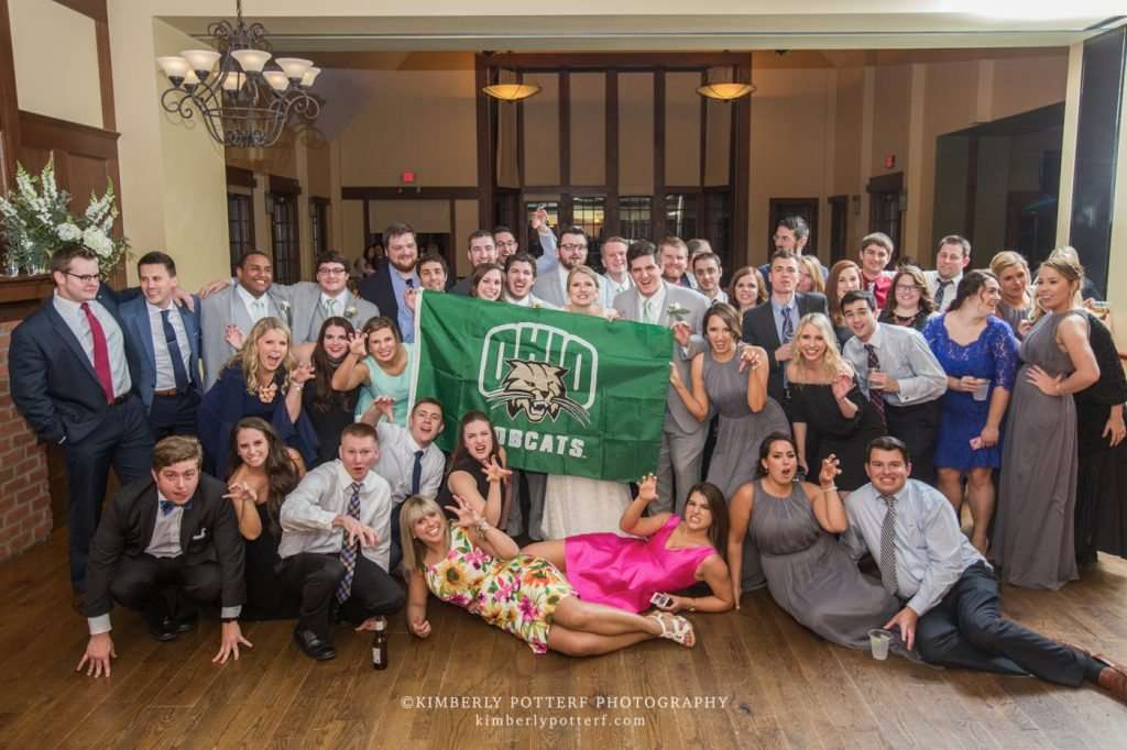large group photo of Ohio University graduates at a wedding reception