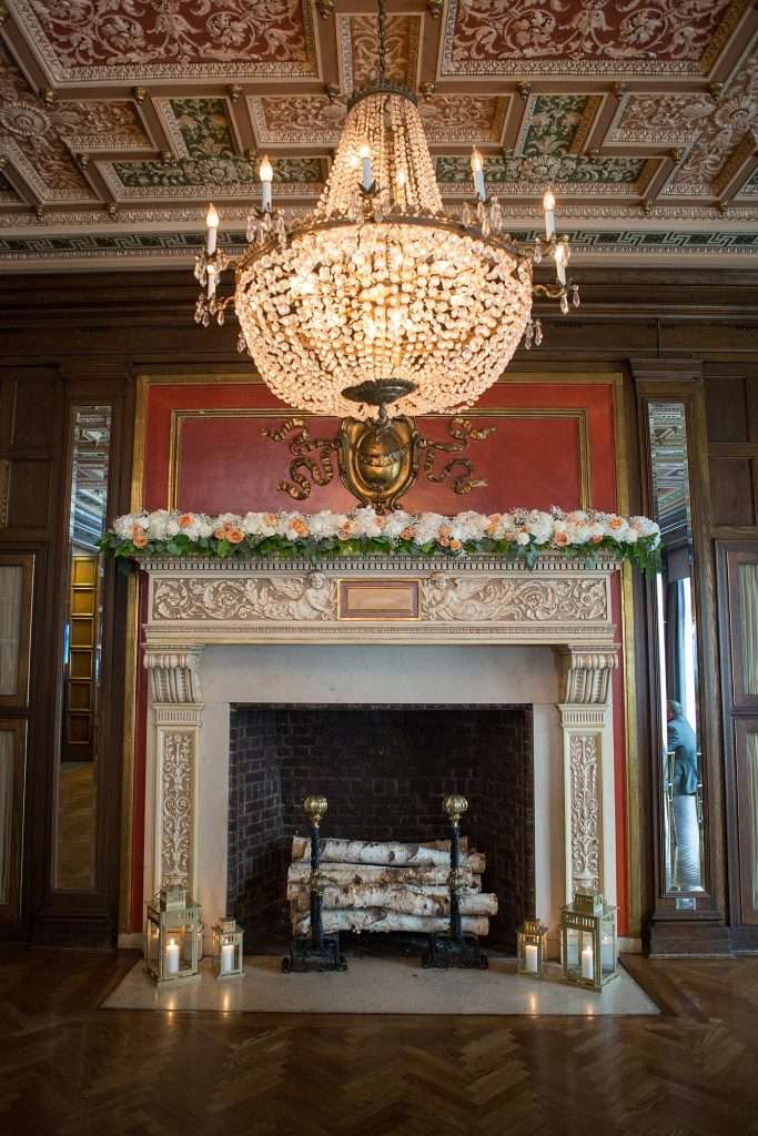 detail shot of fireplace and large crystal chandelier with ornate ceiling detail at the Athletic Club of Columbus