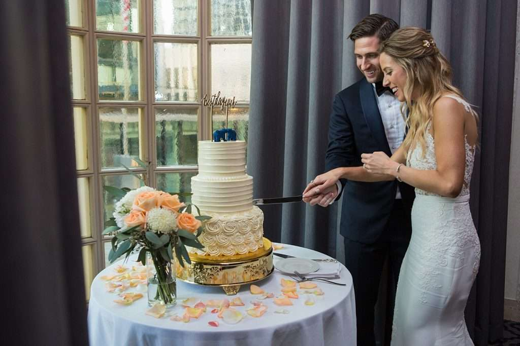 bride and groom cutting their three-tiered cake in front of a window