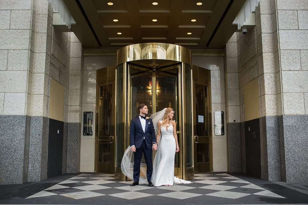 a very stylish bride and groom wearing a dark blue tux and sleek lace Pronovias wedding gown