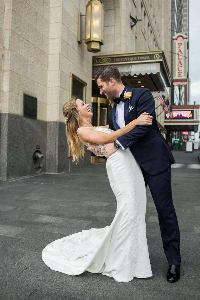 downtown city setting, a groom playfully dips his bride