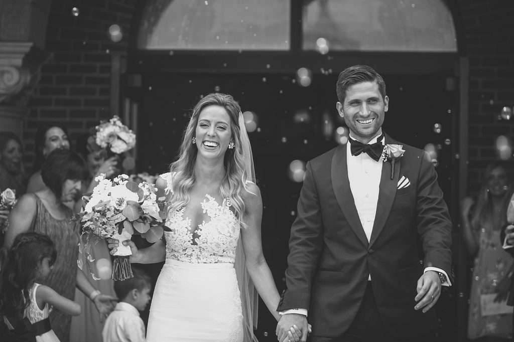 newlywed bride and groom holding hands and smiling while exiting a church