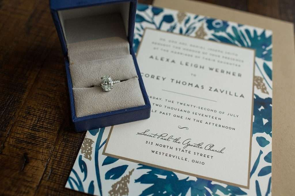 close-up detail shot of a diamond engagement ring and wedding invitation