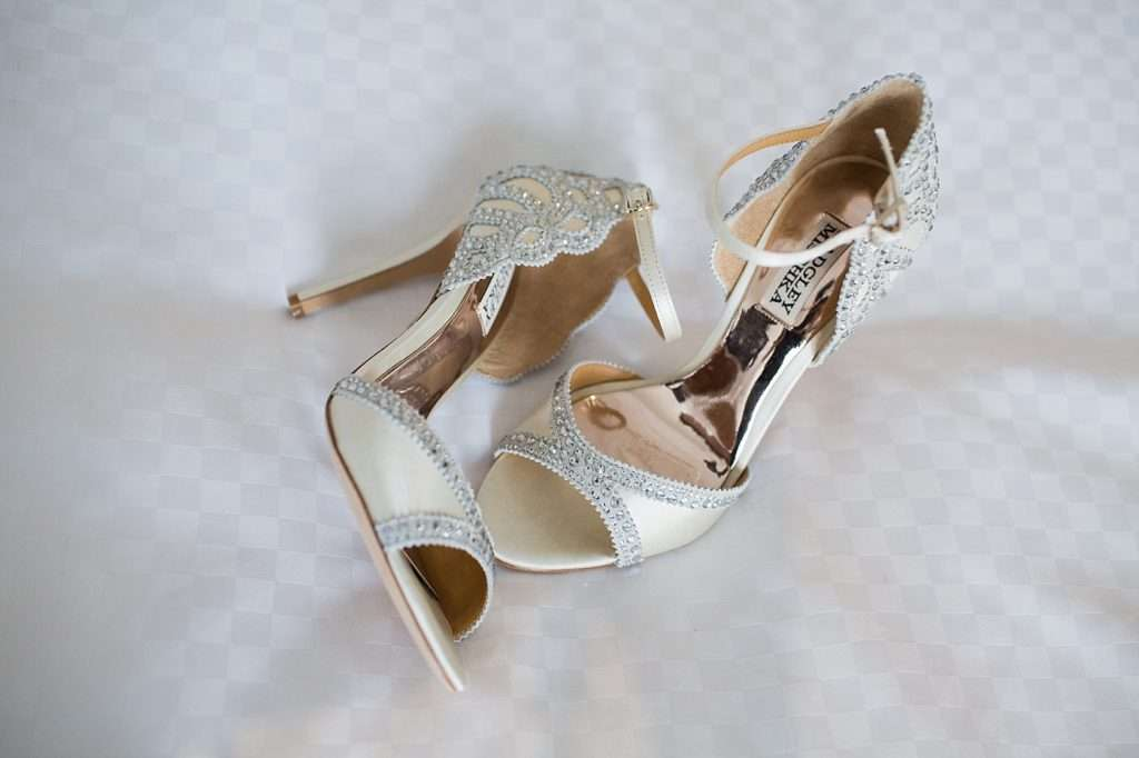 detailed shot of a paid of high heel ivory bridal shoes with crystals