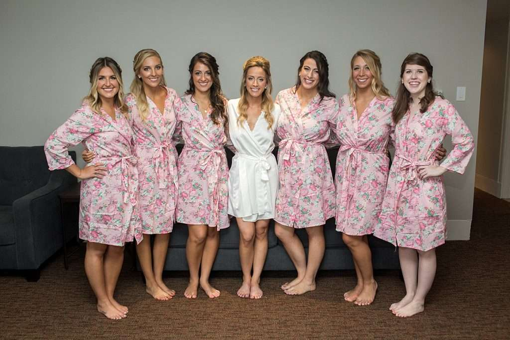 group shot of a bridal party wearing matching pink floral robes