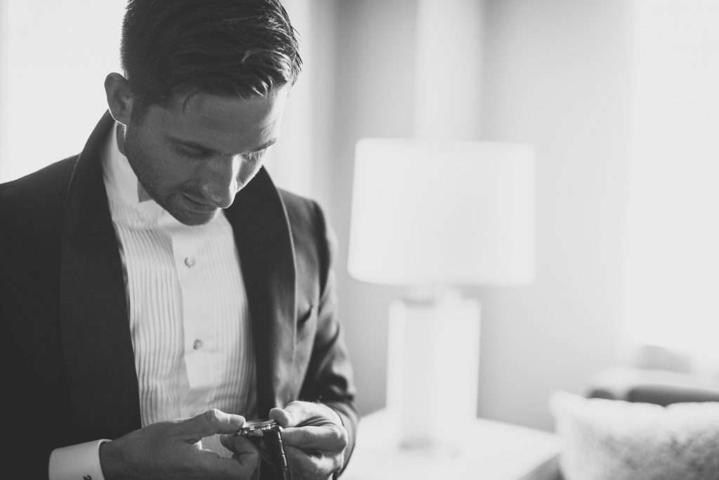 close-up shot of a groom looking at a watch he just received from his bride