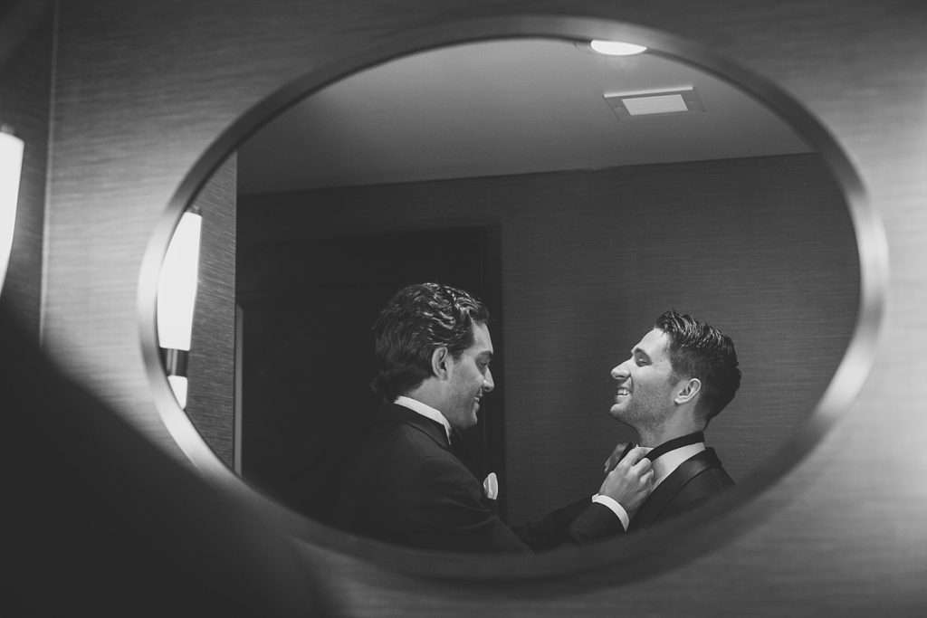 shot of a reflection in a mirror of groomsmen in a room at the Hotel Leveque getting ready for a wedding