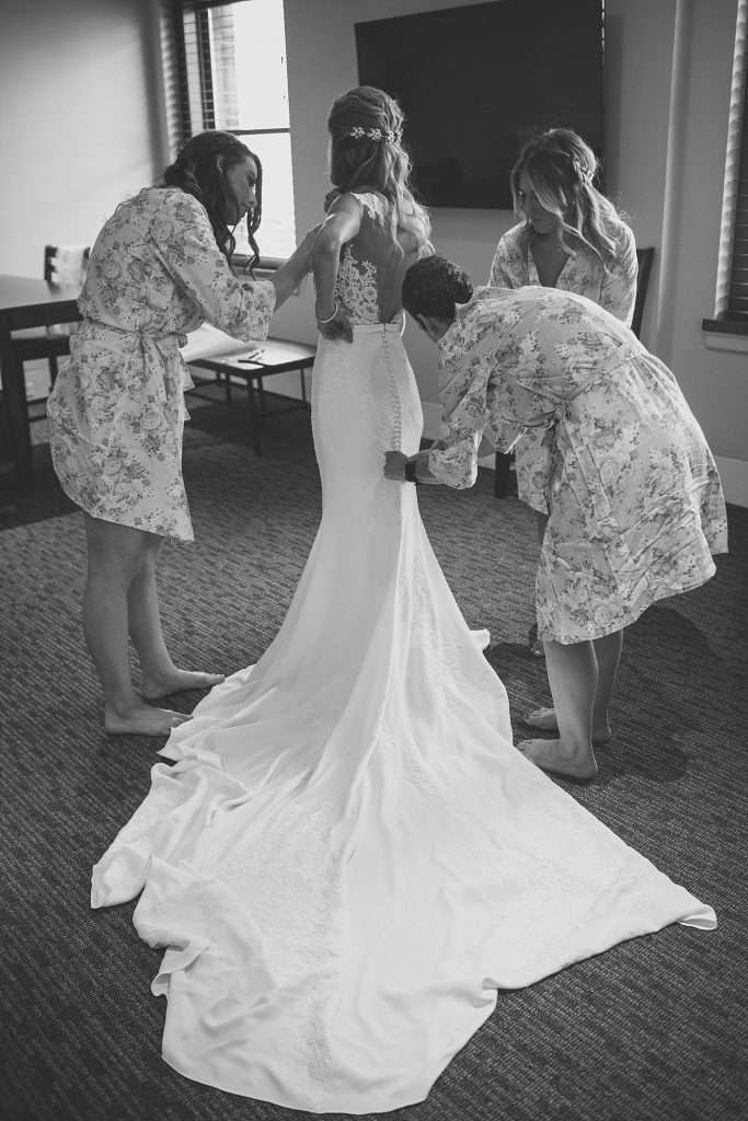 bride getting ready for her wedding day with her mother and bridesmaids
