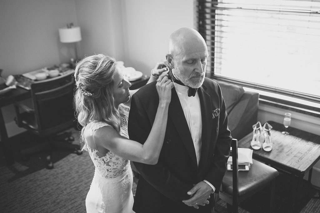 a bride helps her father put on his bowtie