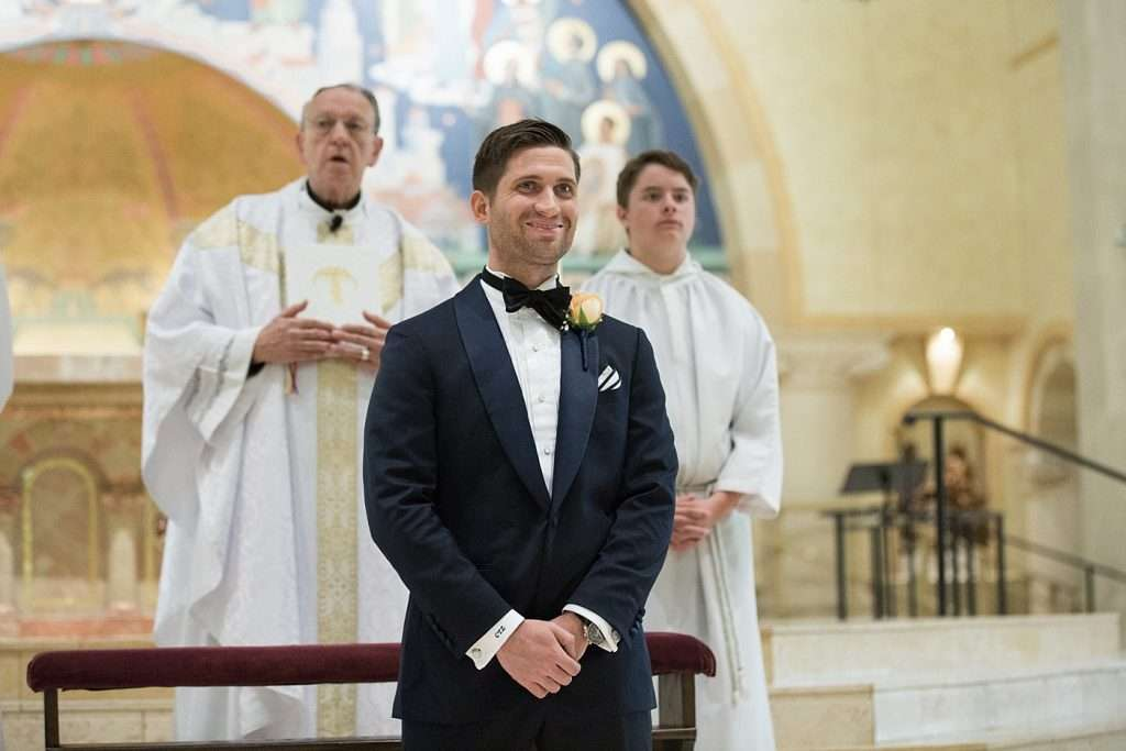 a smiling groom watches his bride walk down the aisle during a wedding ceremony
