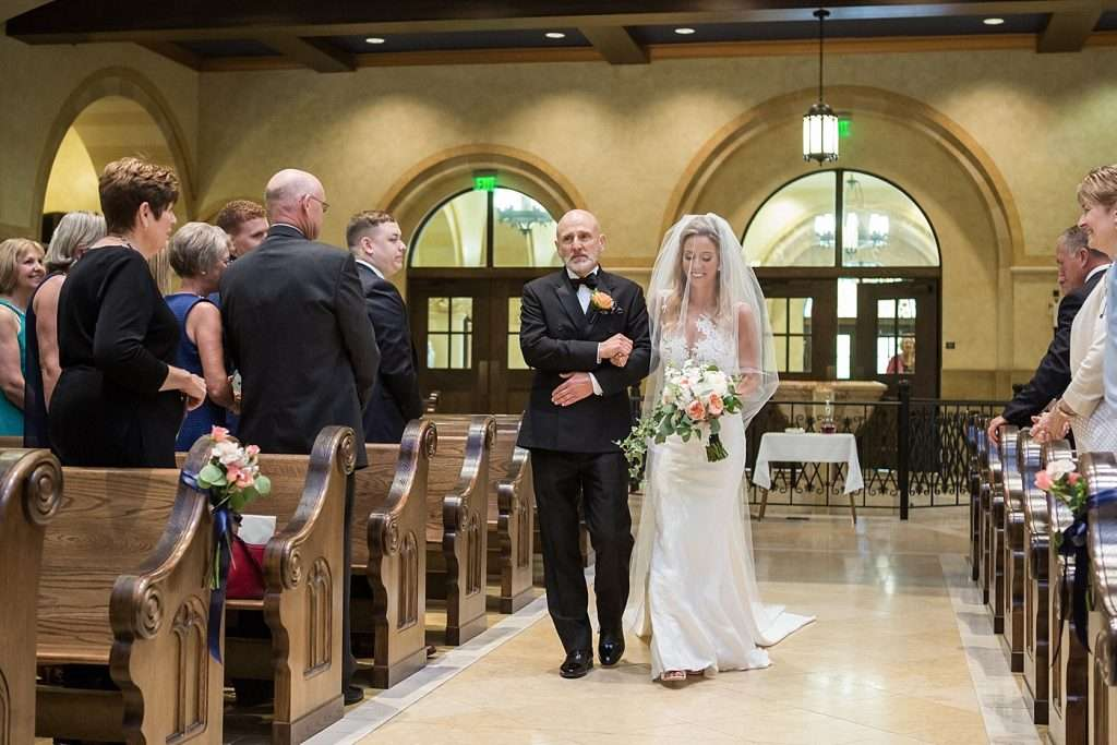 a bride being escorted down the aisle by her father