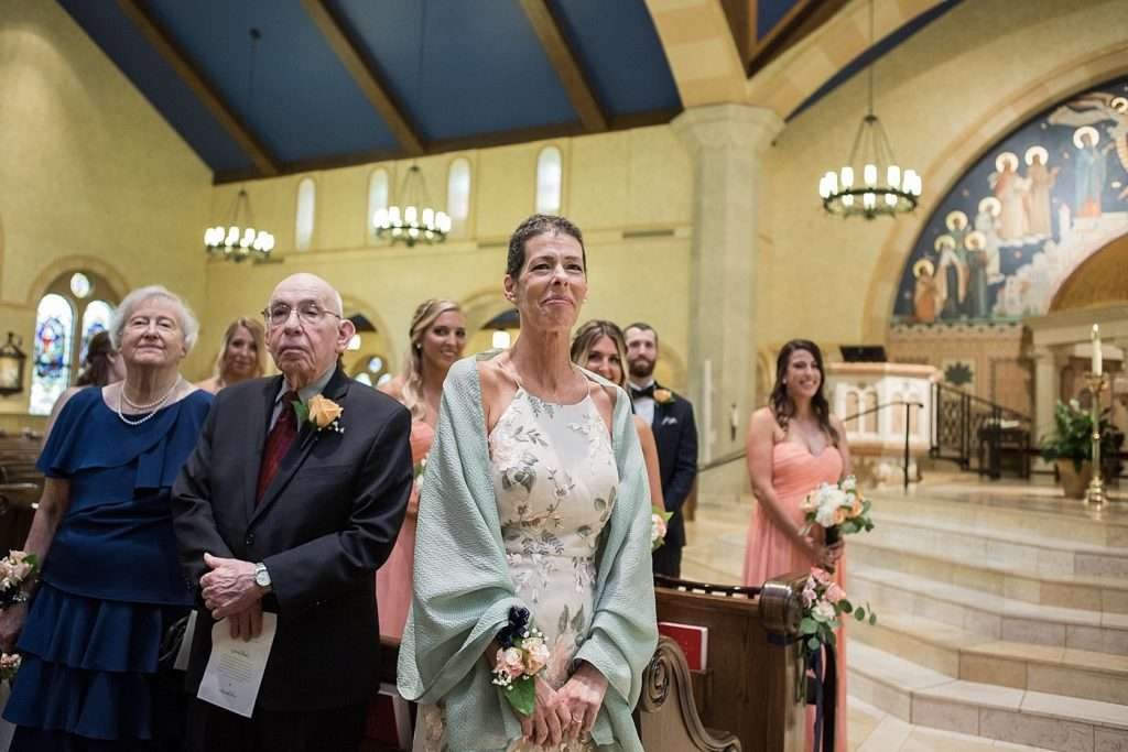 a mother looks at her daughter as she walks down the aisle with her father during a wedding ceremony