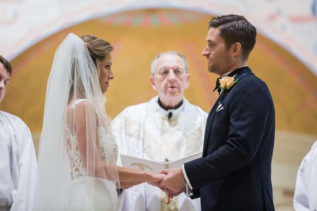 a bride and groom holding hands on the altar during their Catholic wedding ceremony