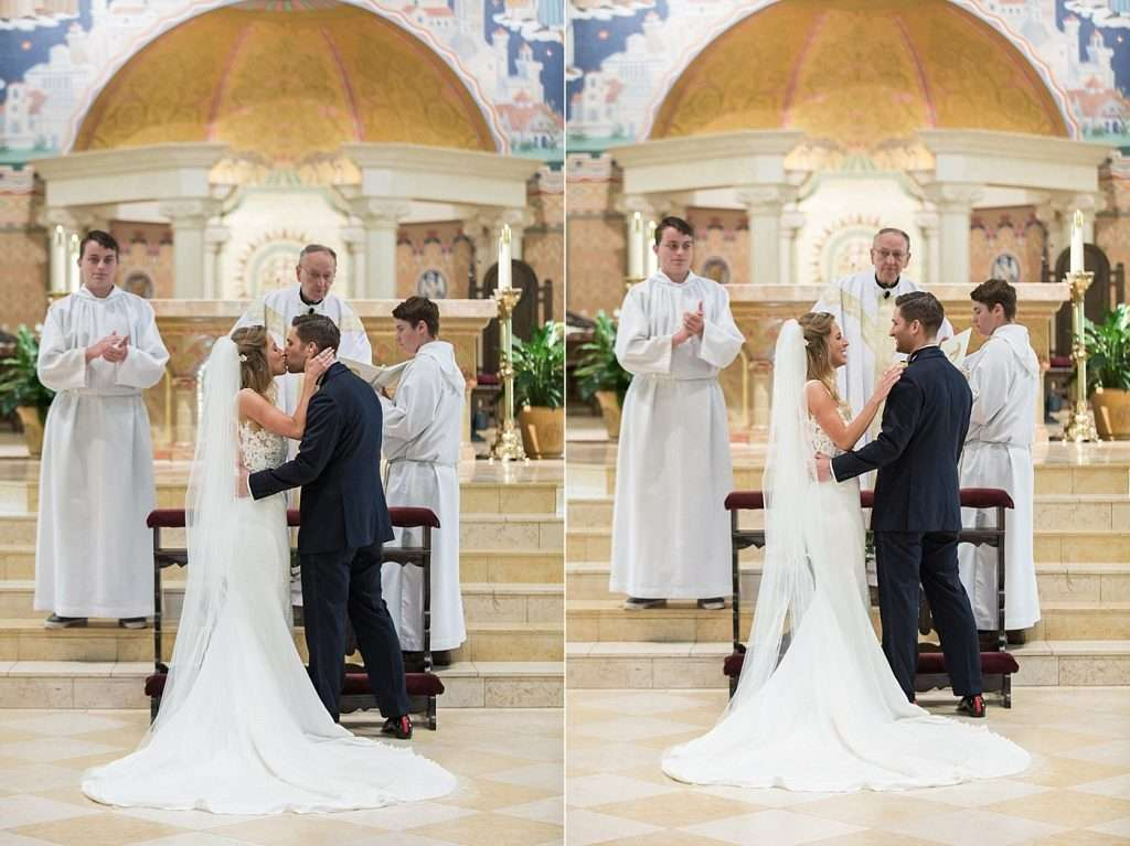 a bride and groom exchange their first kiss during their wedding ceremony