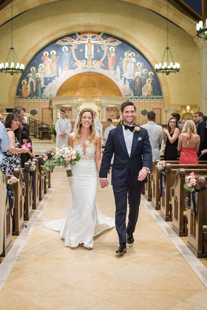 a newly wedded bride and groom holding hands and smiling walking out of the church