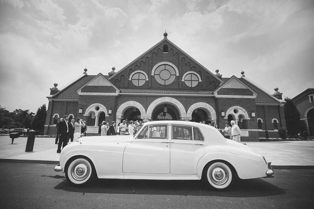 black and white image of a vintage Bentley parked in front of a large Catholic Church for a wedding