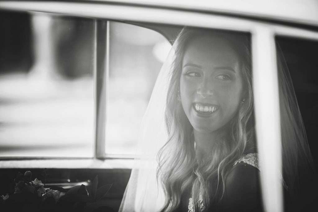a happy bride peers out of the window of their vintage limousine