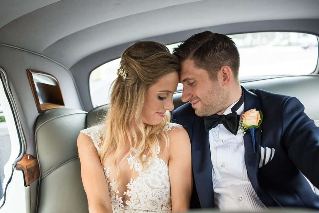 a bride and groom cuddle and smile inside a vintage Bentley getaway car on their wedding day