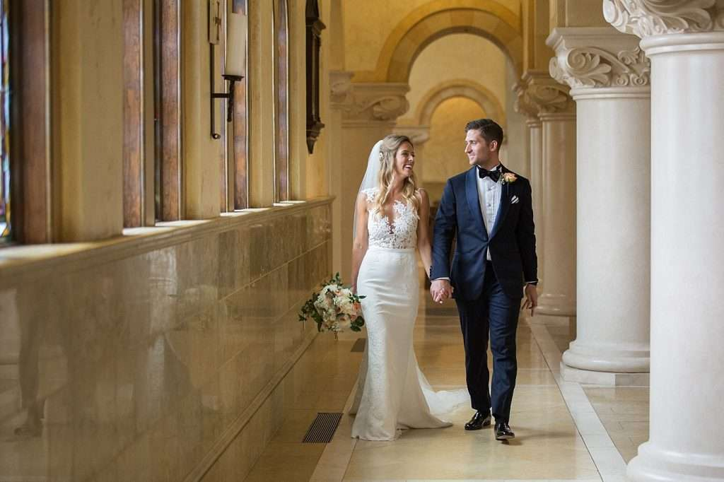 bride and groom walking together inside a church with stained glass windows