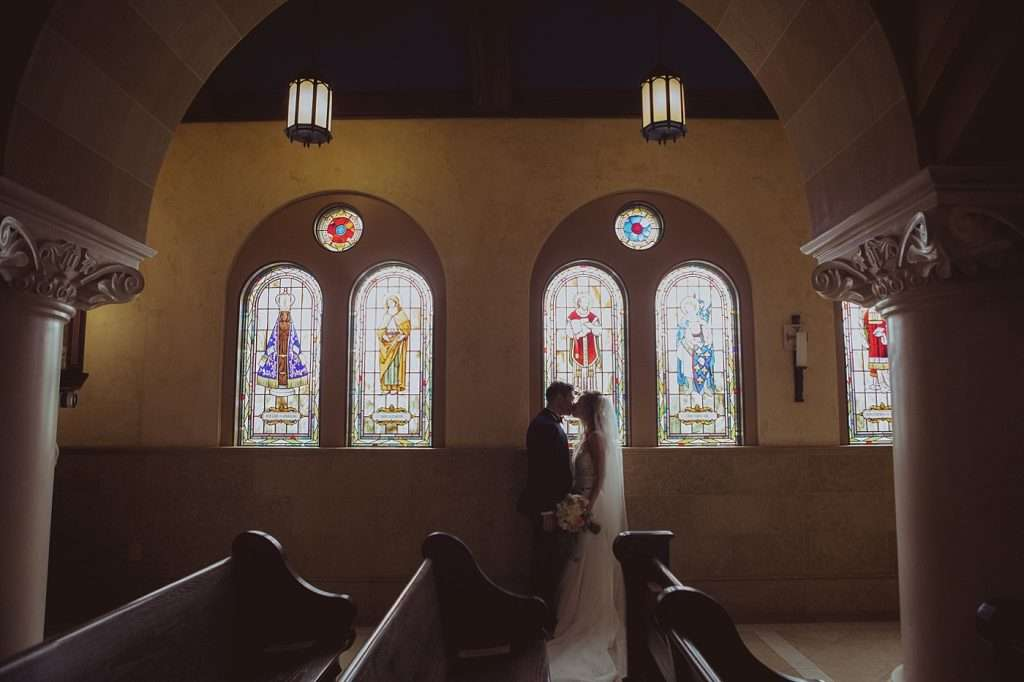 bride and groom kissing in front of a wall of stained glass windows with dramatic lighting