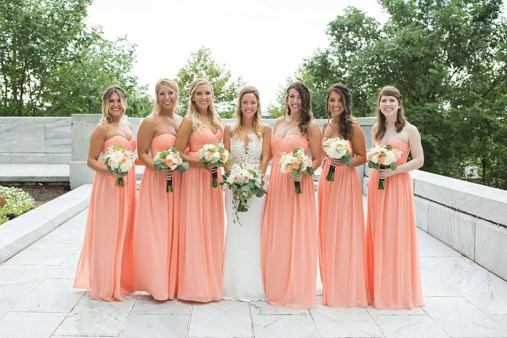 bridesmaids wearing long peach dresses and carrying ivory and peach bouquets