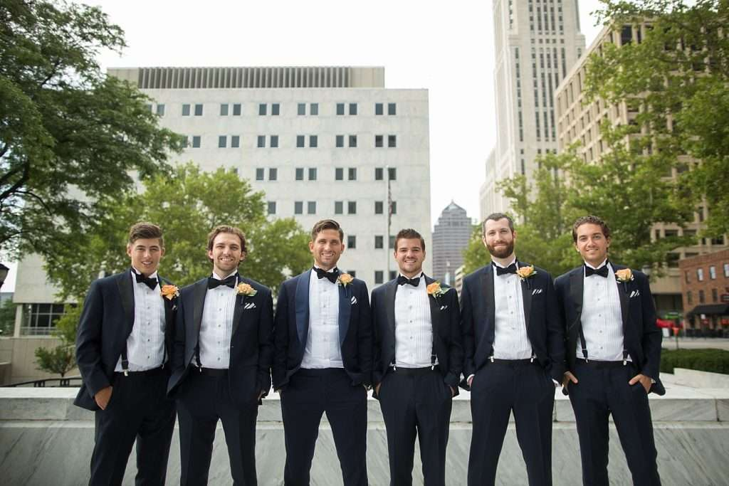 groomsmen posing together downtown wearing navy blue tuxedos with black lapels
