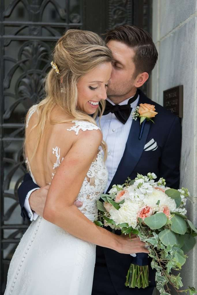 a groom kisses his bride on the cheek, she is holding a bouquet of ivory and peach flowers