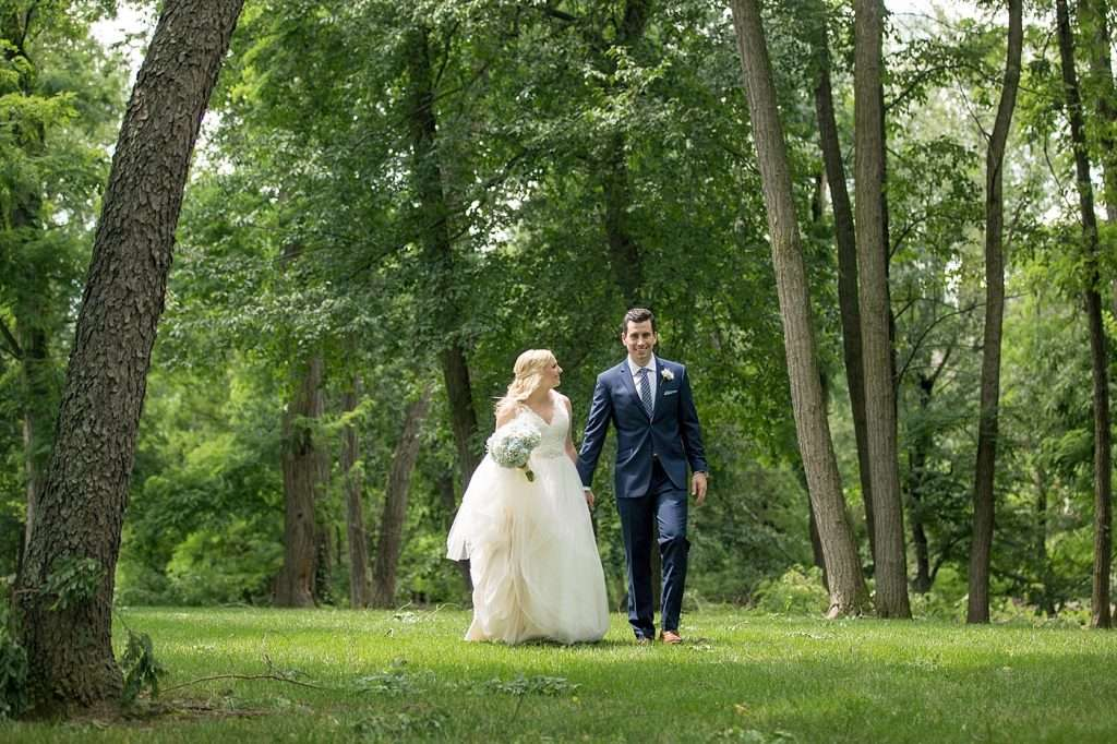 a bride and groom holding hands walking through a wooded area with tall trees