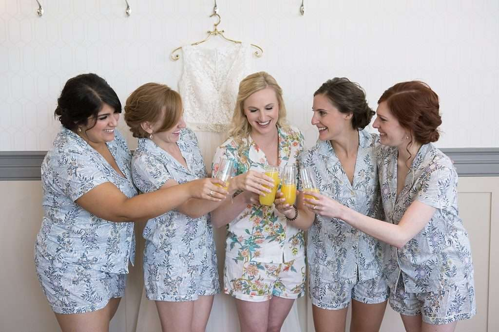 a bride and her bridesmaid are wearing coordinating floral print pajamas and toasting with mimosas on the morning of the wedding, the bridal gown is hanging behind them