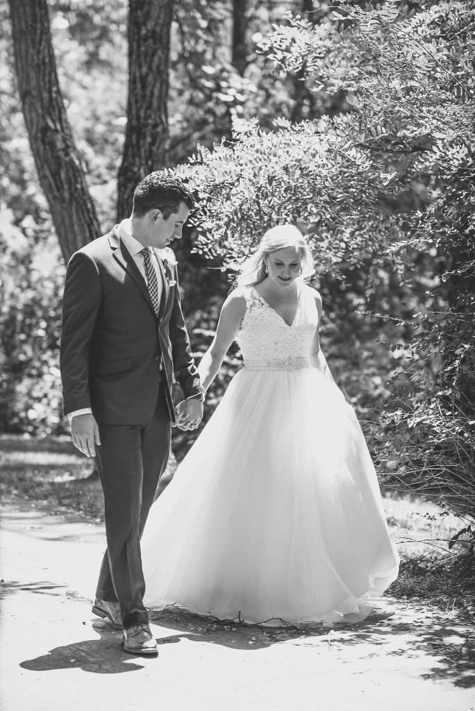 bride wearing a v-neck lace gown holding hands with her groom while walking through a wooded park