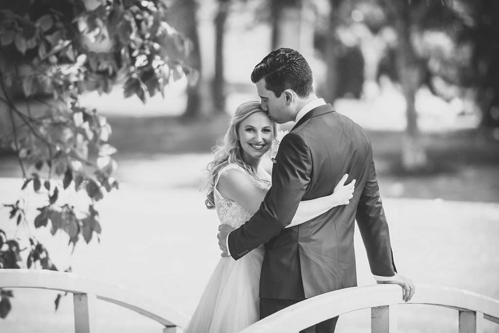 natural relaxed portrait of a bride looking at the camera with her groom kissing her forehead