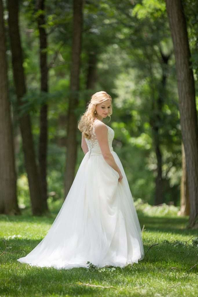 bride with long blonde hair wearing a lace and organza illusion back dress walking through a wooded area with tall trees