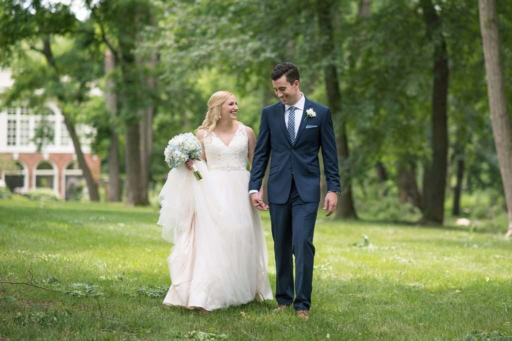bride and groom holding hands smiling and walking through a woodsy setting of tall trees