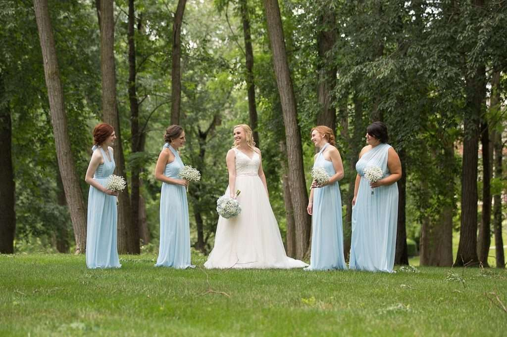 bride and bridesmaids wearing light blue dresses holding white baby's breath bouquets standing in a woodsy setting of tall trees