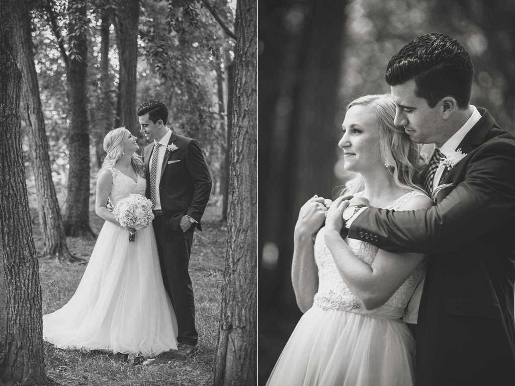 romantic black and white image of a bride and groom hugging in a woodsy rustic setting