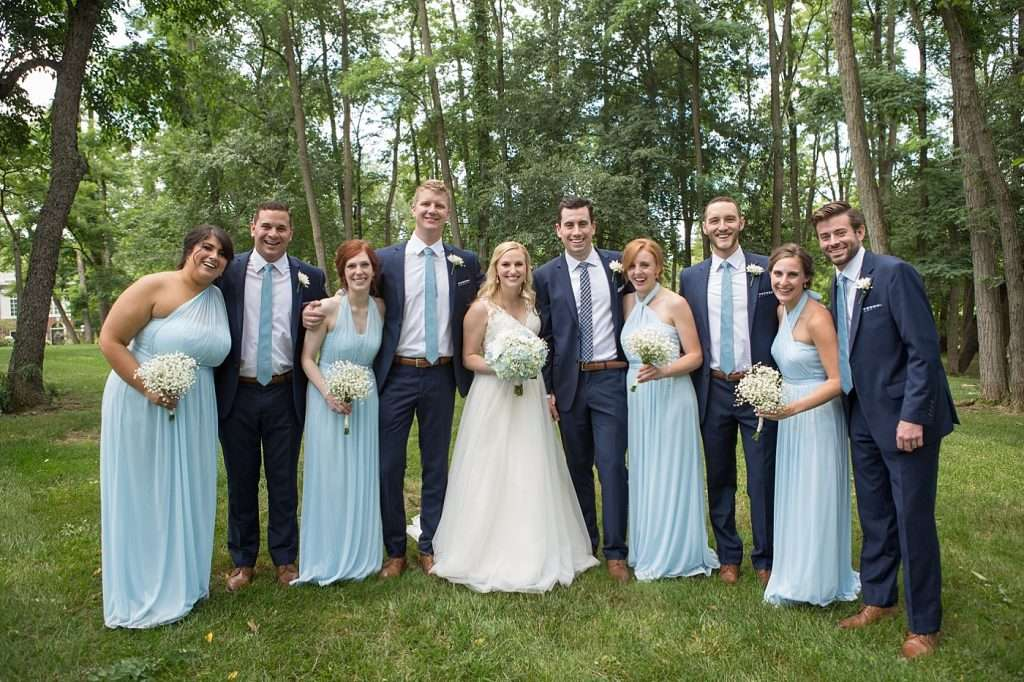 bridal party wearing dark blue suits and light blue dresses standing together laughing