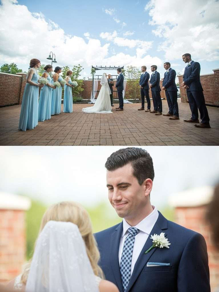 bridesmaids wearing light blue dresses and groomsmen wearing navy suits standing during a wedding ceremony