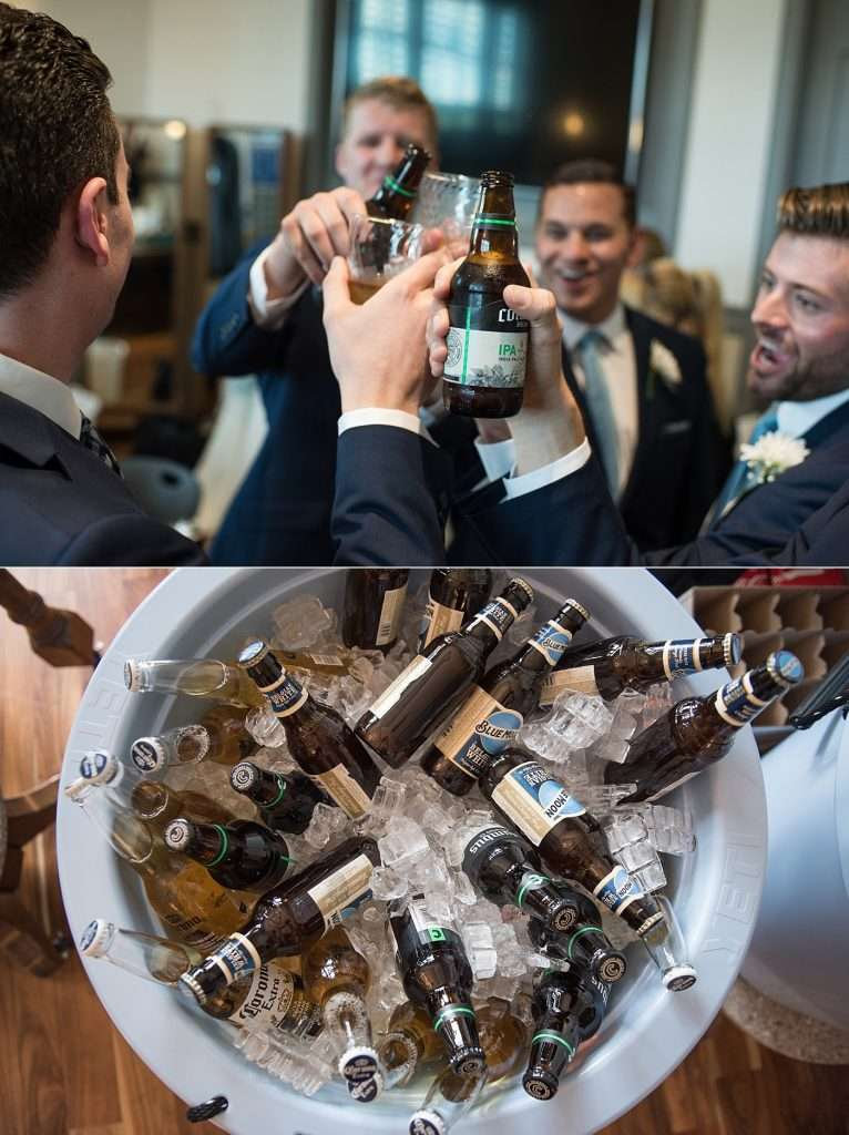 close-up image of a group of groomsmen toasting beer bottles