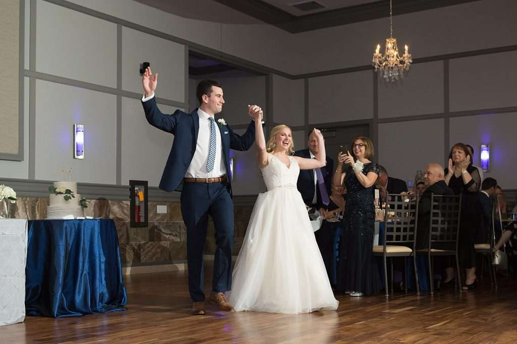bride and groom entering their wedding reception, smiling with hands in the air, guests clapping