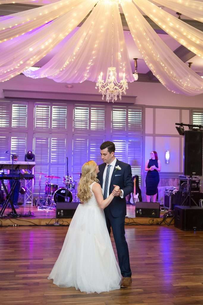 bride and groom dancing at their wedding reception, backdrop of purple lighting
