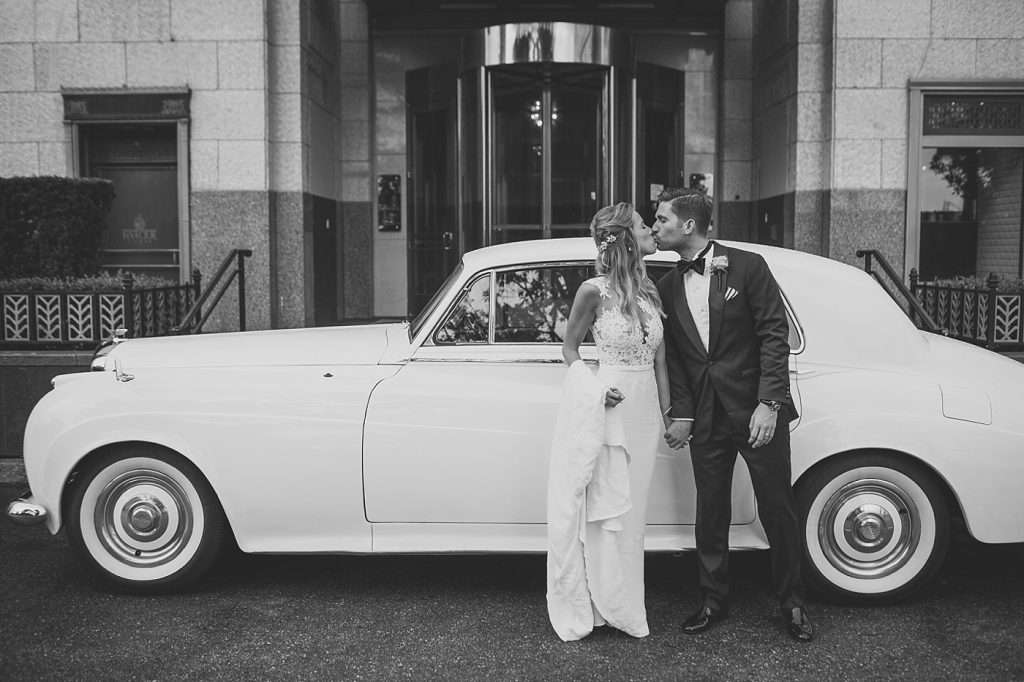 newlywed couple kissing in front of a vintage getaway car