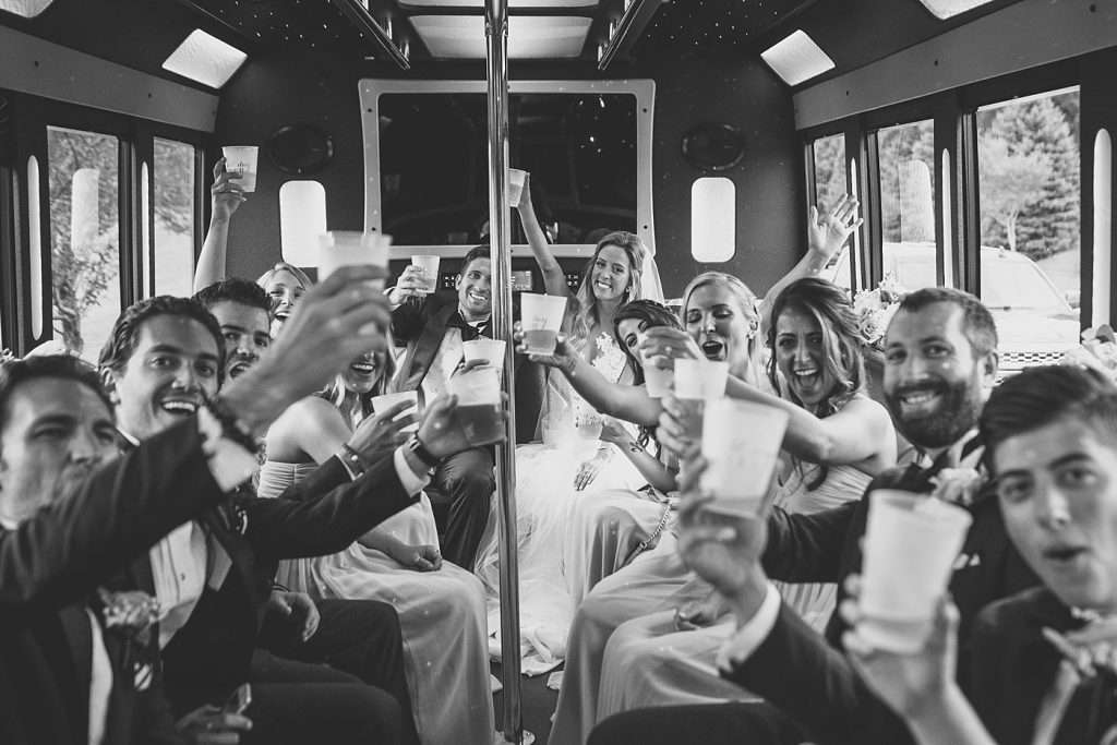 a rowdy wedding party aboard a party bus raises their glasses to cheer