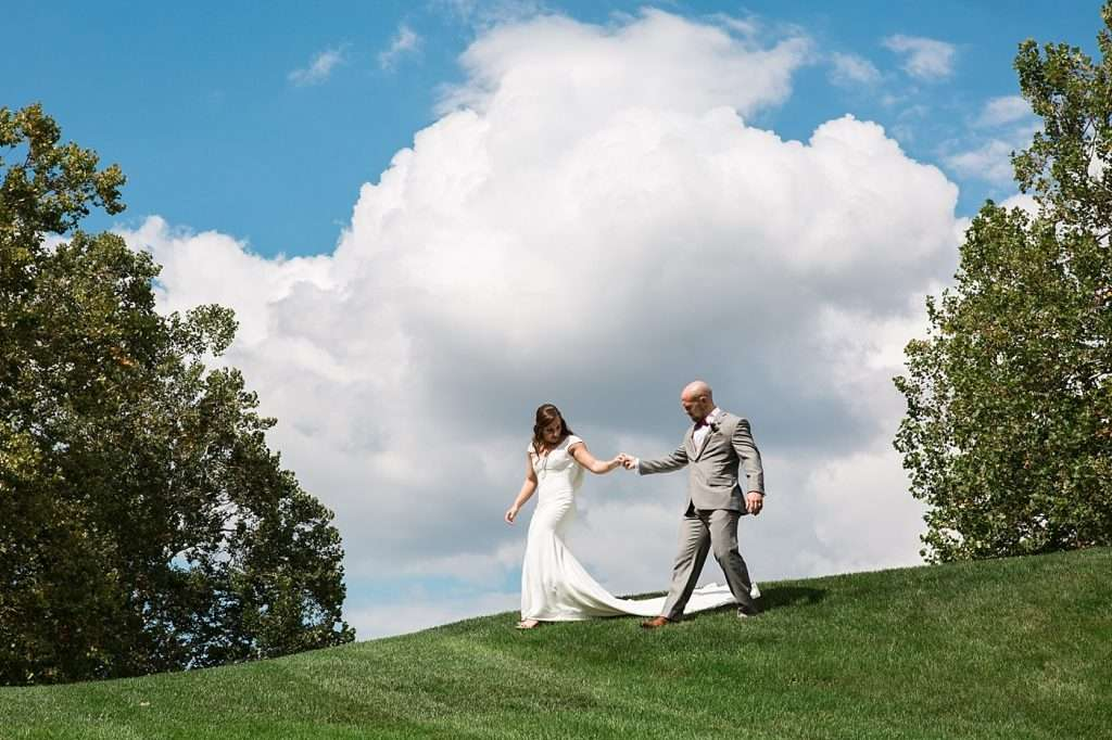 bride and groom walking down a hillside on a bright sunny day with white puffy clouds in the sky