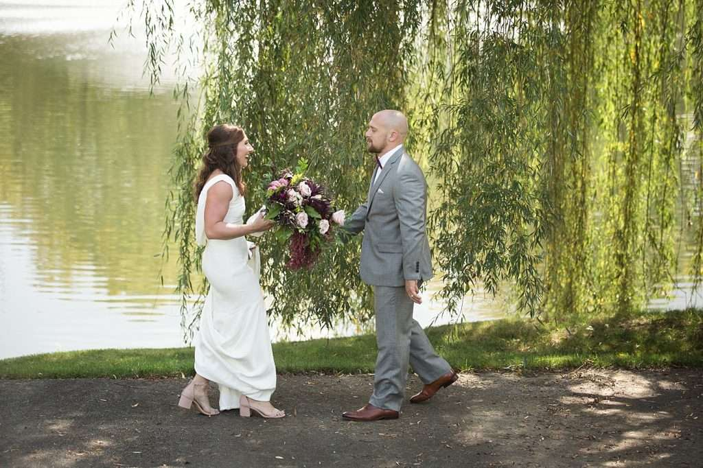 wide angle shot of a bride and groom greeting each other on their wedding day under a large willow tree